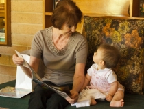 Lilia reading a book with Great Auntie Anita
