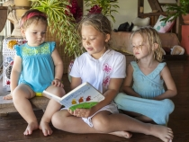 Anna reading a story to Lilia and Sophia