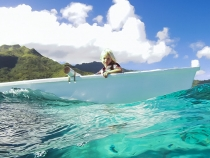 Sophia in the outrigger over the reef with Moorea in the background