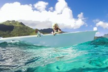 Sophia in the outrigger over the reef with Moorea in the backgro