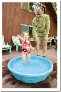 Lilia enjoying her pool with Grandpa on the deck at the cabin